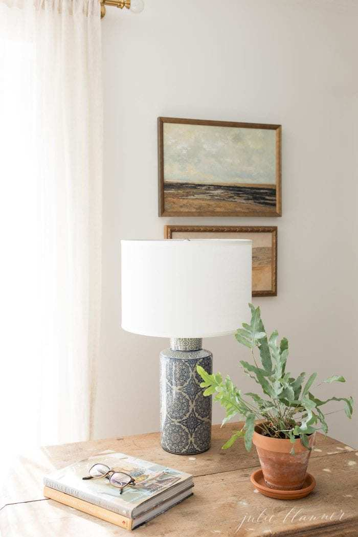 plant lamp books on antique table with painted art and curtains in background