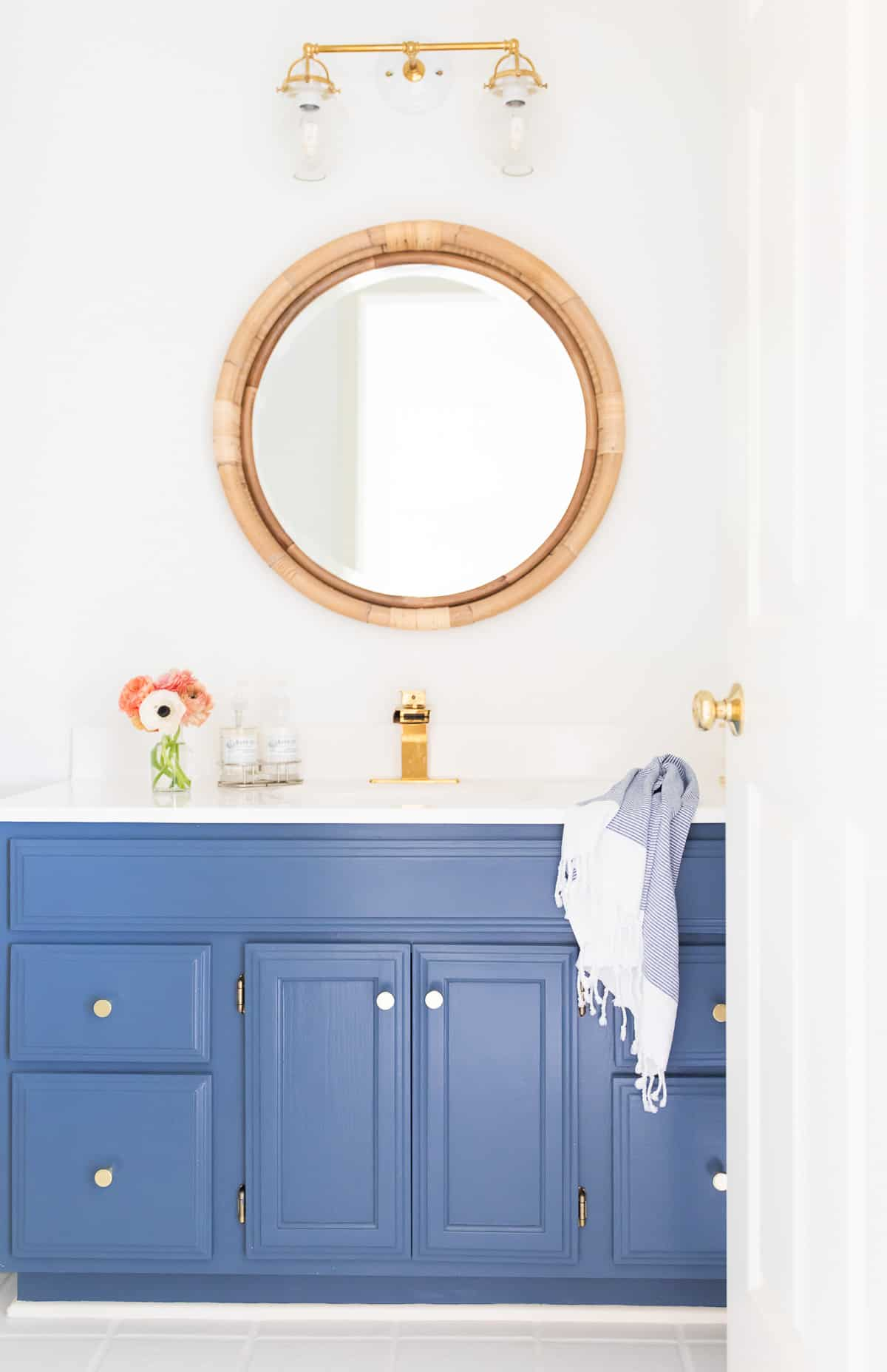 white and brass light on wicker mirror and blue dressing table