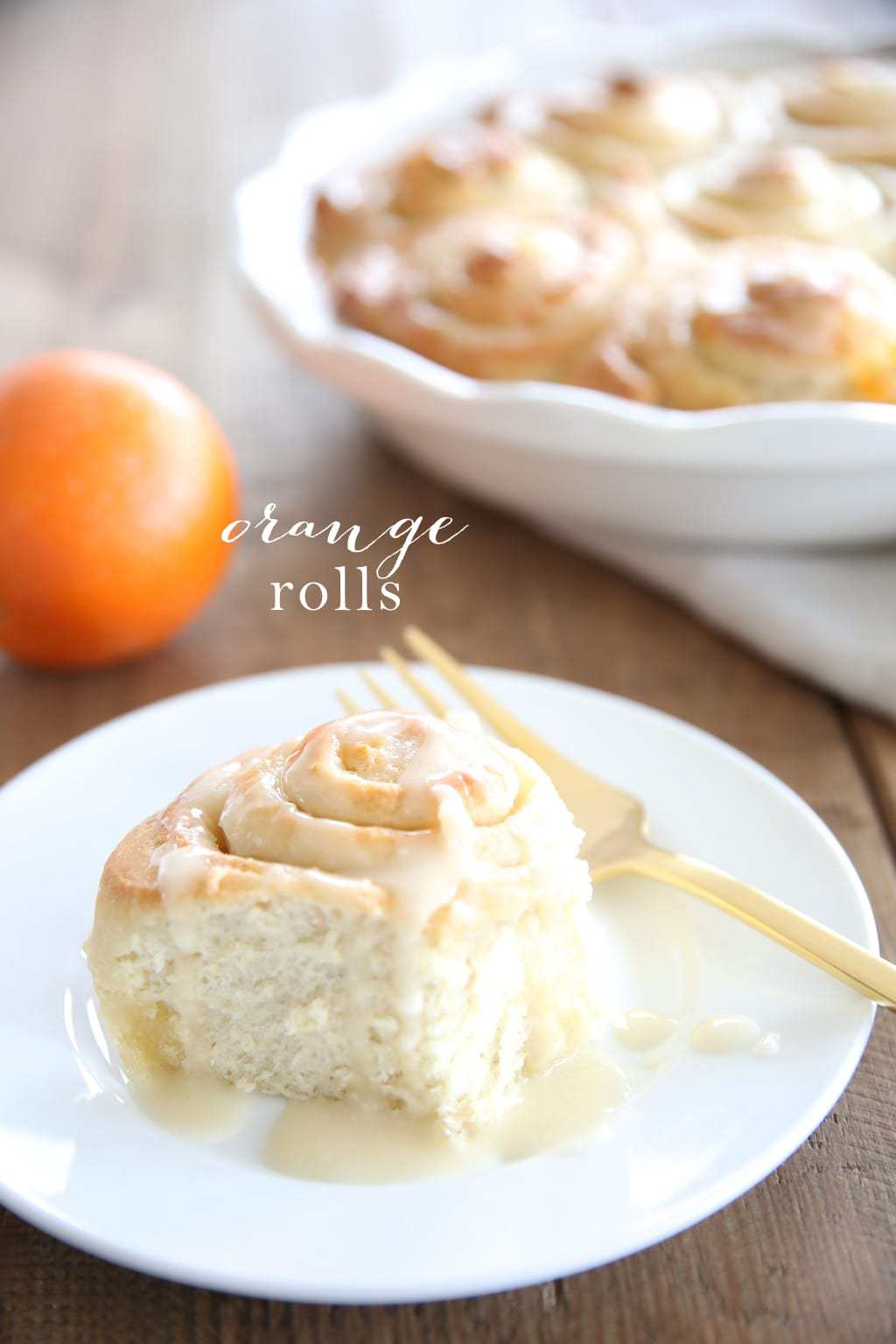 An orange roll served on a white pate with a text overlay 'orange rolls'