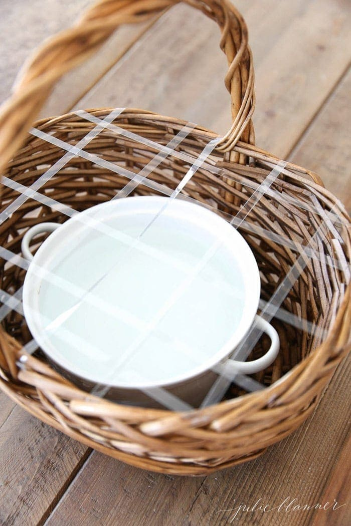 basket with tape over a dish inside prepping for a floral arrangement.