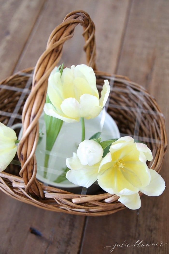 The beginning of an arrangement of yellow tulips in a flower basket