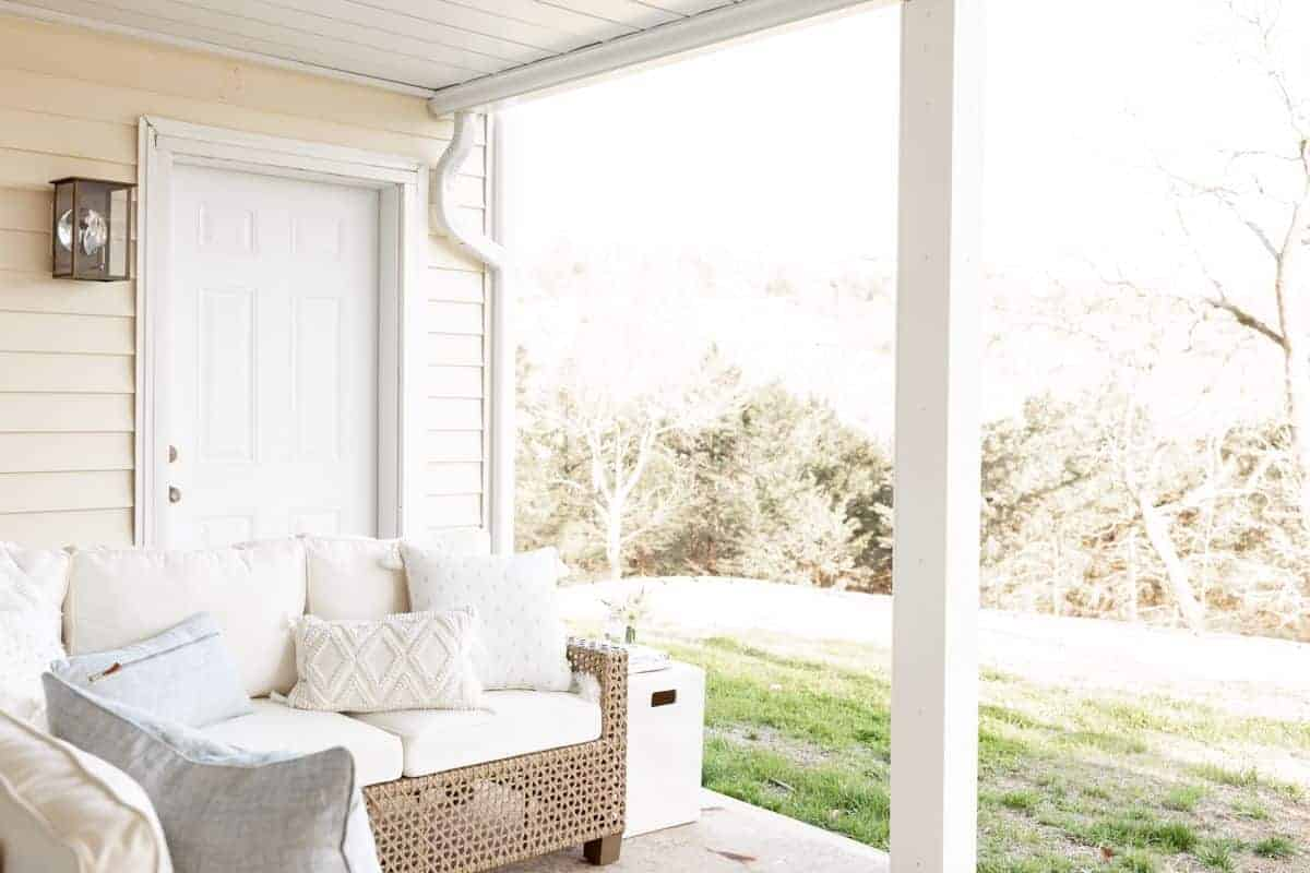 An outdoor room patio scene with a white sectional and flowers on a side table, white underdecking ceiling above.