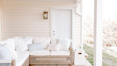 A patio with an under deck drainage system above, with a white rattan sectional.