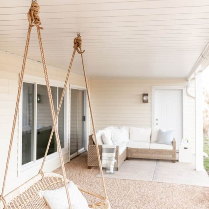 An outdoor room with a white under deck ceiling, rattan swing and sectional sofa as focal points.