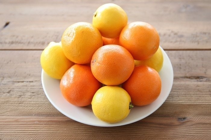 Lemons and oranges on a white plate on a wooden table.