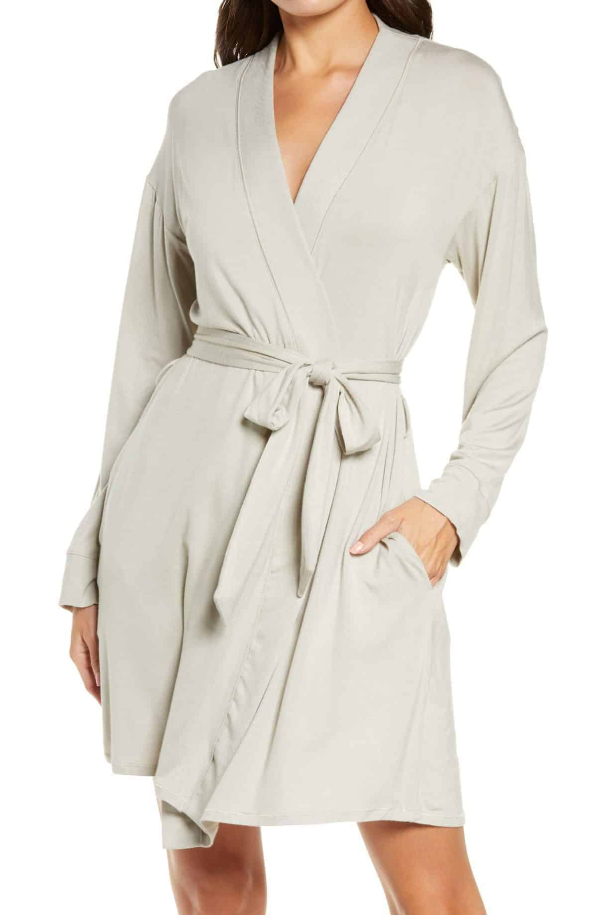 Product shot of a model wearing a soft ivory robe, white background.