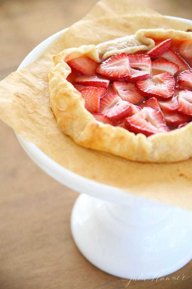 The baked strawberry tart on a cake stand