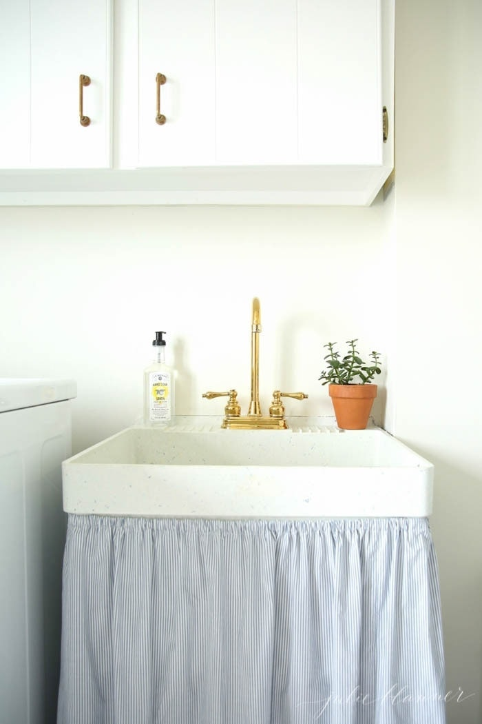 A white laundry room with a houseplant on the ledge of the sink.