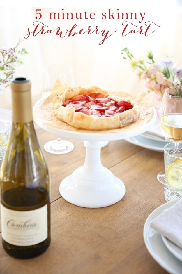 A strawberry tart on a cake stand next to a bottle of wine