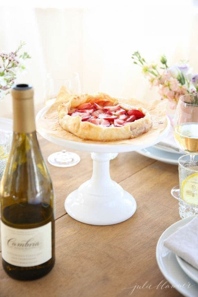 The quick strawberry tart served on a white cake stand