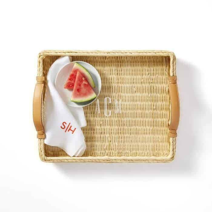 A wicker and leather tray on a white surface, slice of watermelon and a napkin on the tray.