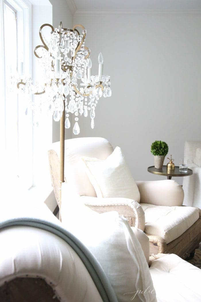 Rustic Restoration Hardware chairs with a crystal and gold floor lamp for luxury home decor in a white living room.