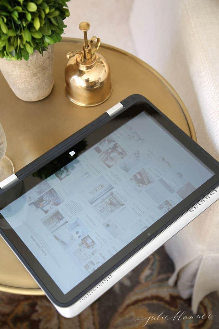 A gold side table with an ipad on top.