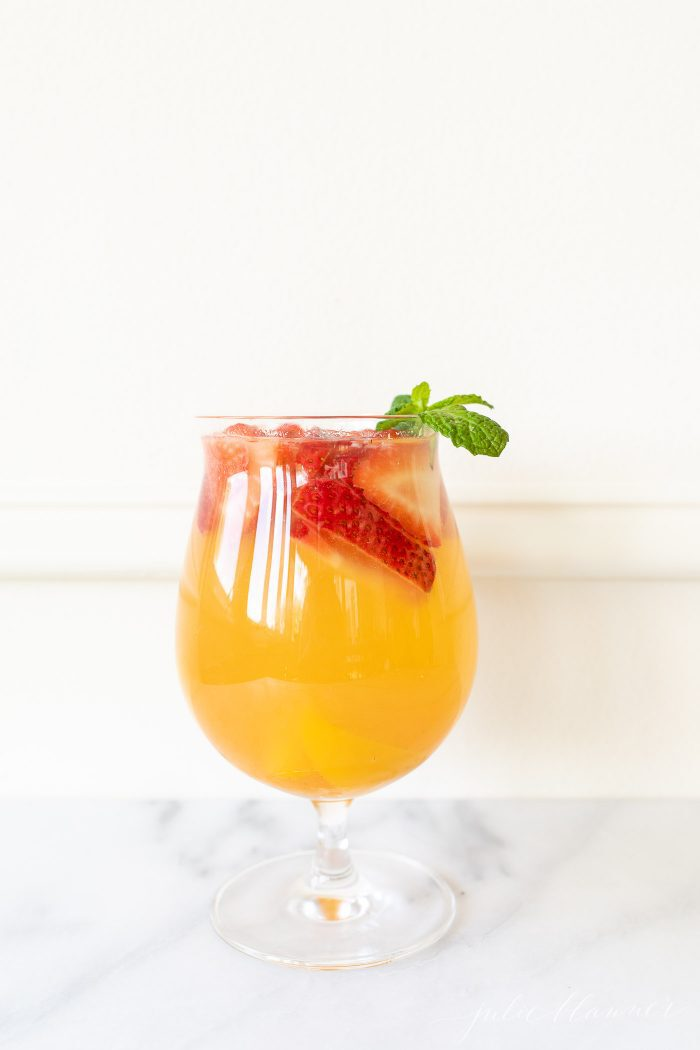 fruity sangria recipe in a glass garnished with strawberries peaches and mint