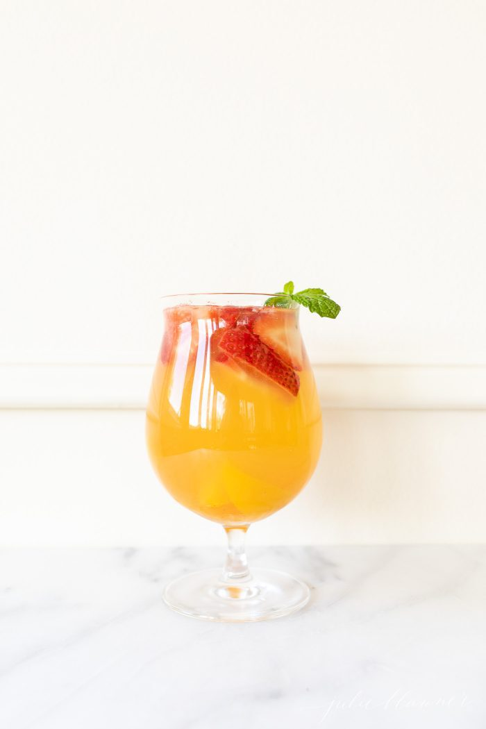 peach sangria in a glass a fruity sangria recipe garnished with mint