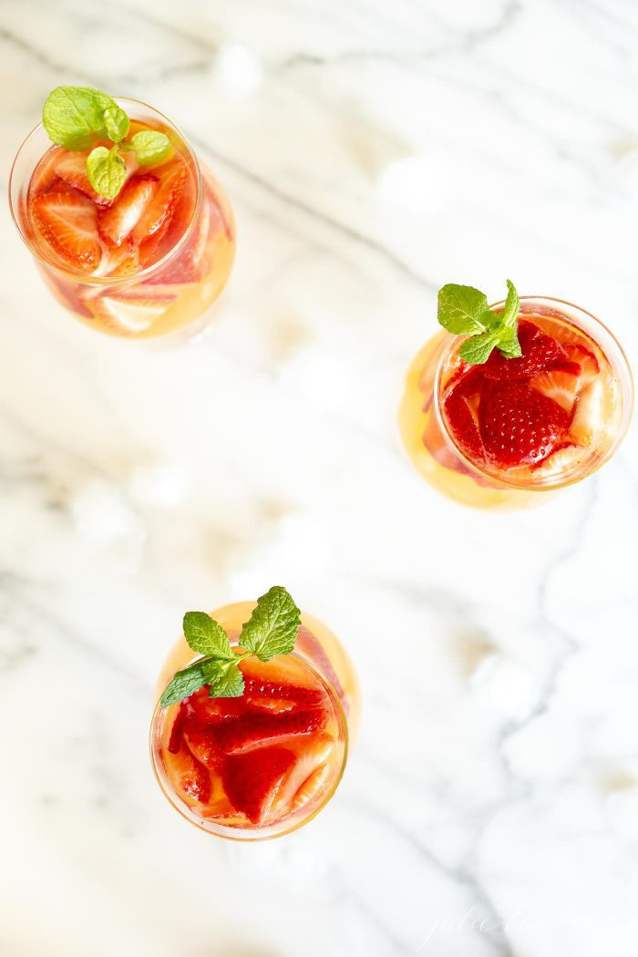 3 glasses of peach sangria topped with strawberries and garnished with mint