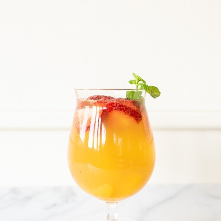 Peach Sangria in a glass, garnished with peaches, strawberries, and mint.