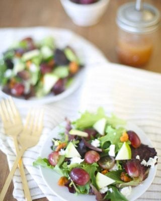 two salads on white plates tossed in raspberry vinaigrette dressing with two gold forks