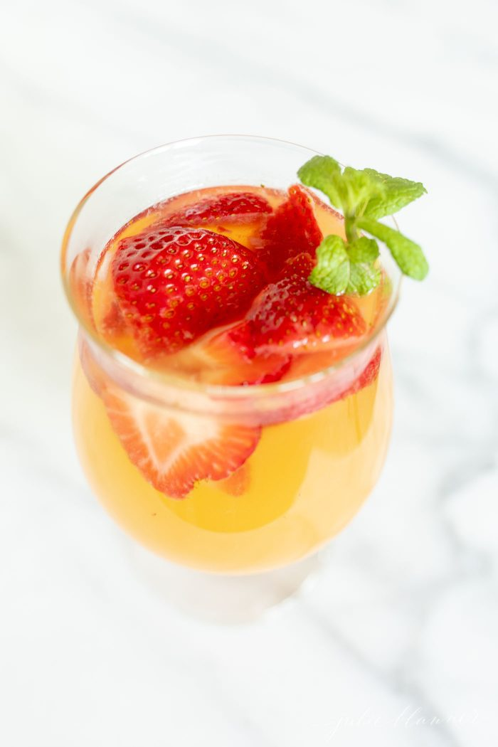 fruity sangria recipe in a glass with peaches, strawberries and garnished with mint