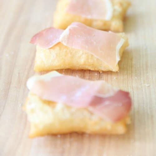A row of gnocco fritto on a wooden surface, topped with prosciutto