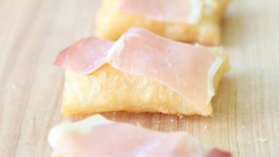 gnocco frito topped with olive oil, prosciutto, and sea salt