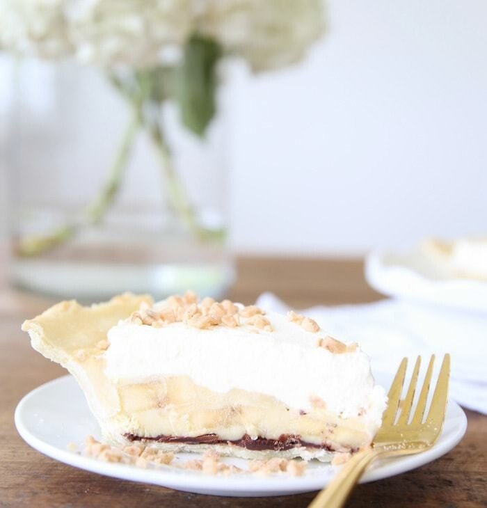 slice of easy banana cream pie recipe on white plate with gold fork with white flowers in glass vase in background