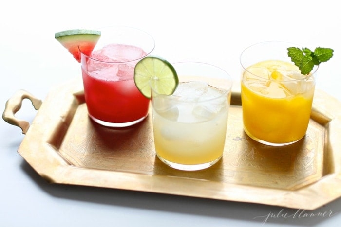 watermelon margarita on a tray with a skinny margarita and mango margarita