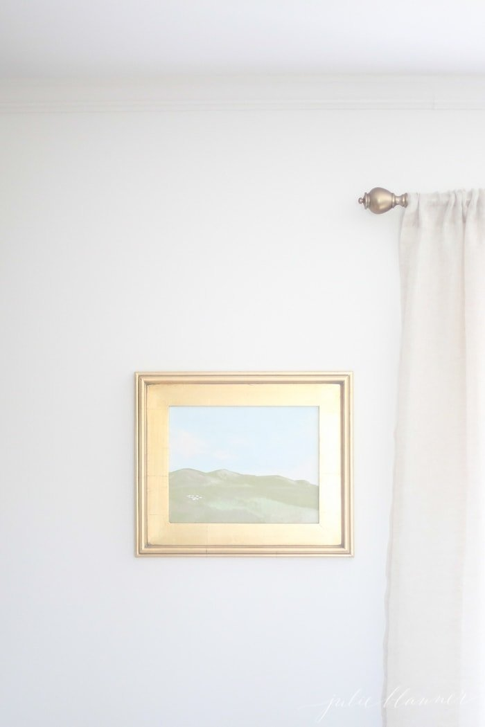 A white wall with a framed oil painting in a gold frame.