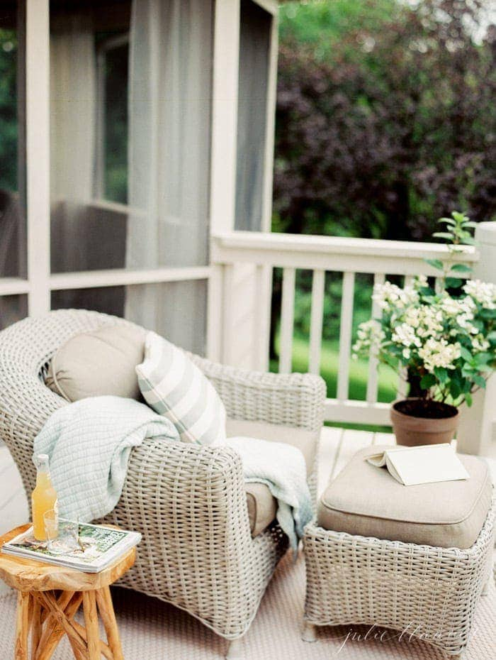 A white deck with wicker furniture and plants for decor.