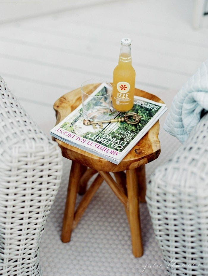 An outdoor living room with a cute side table, magazine and drink on top.