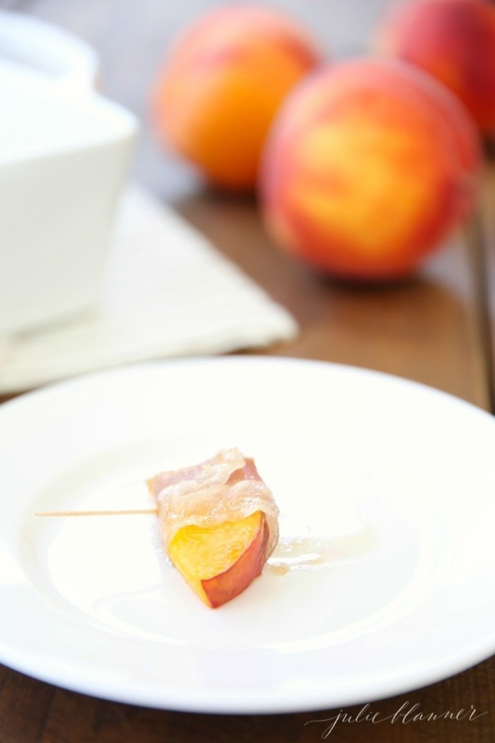 Prosciutto wrapped peach on a skewer on a white plate