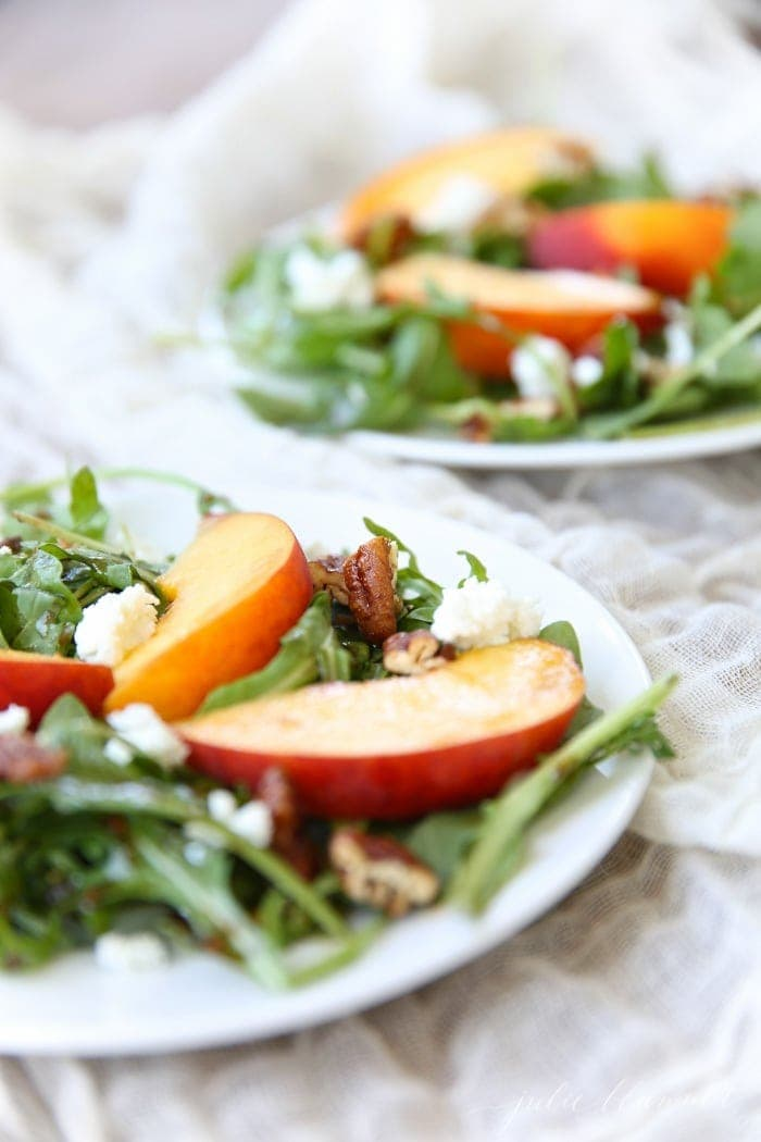 Sliced peaches on a bed of arugula