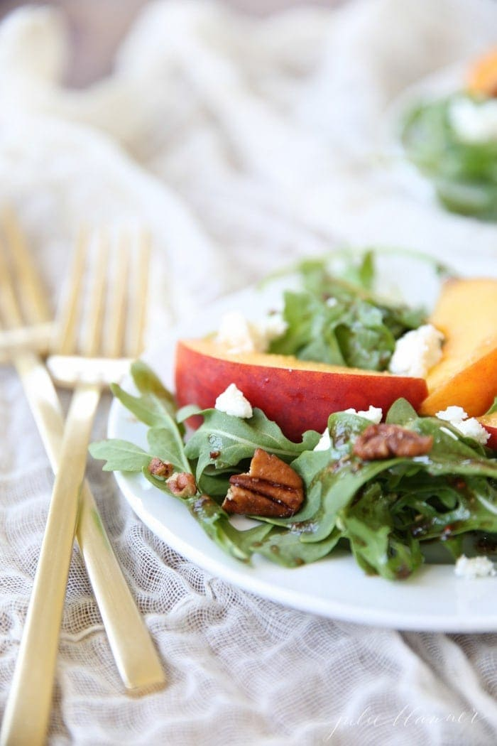Peach salad with vinaigrette served on a white plate with a gold fork