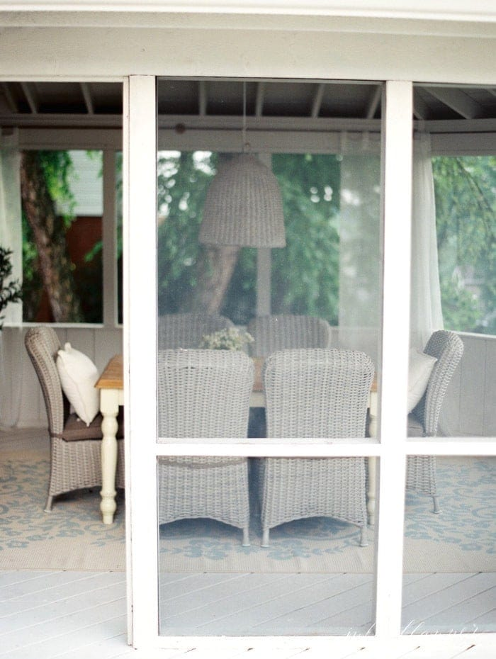 A screened in porch dining room area, outside view.