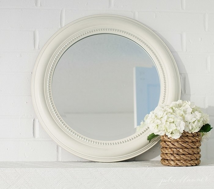 A mirror with a small vase on the side