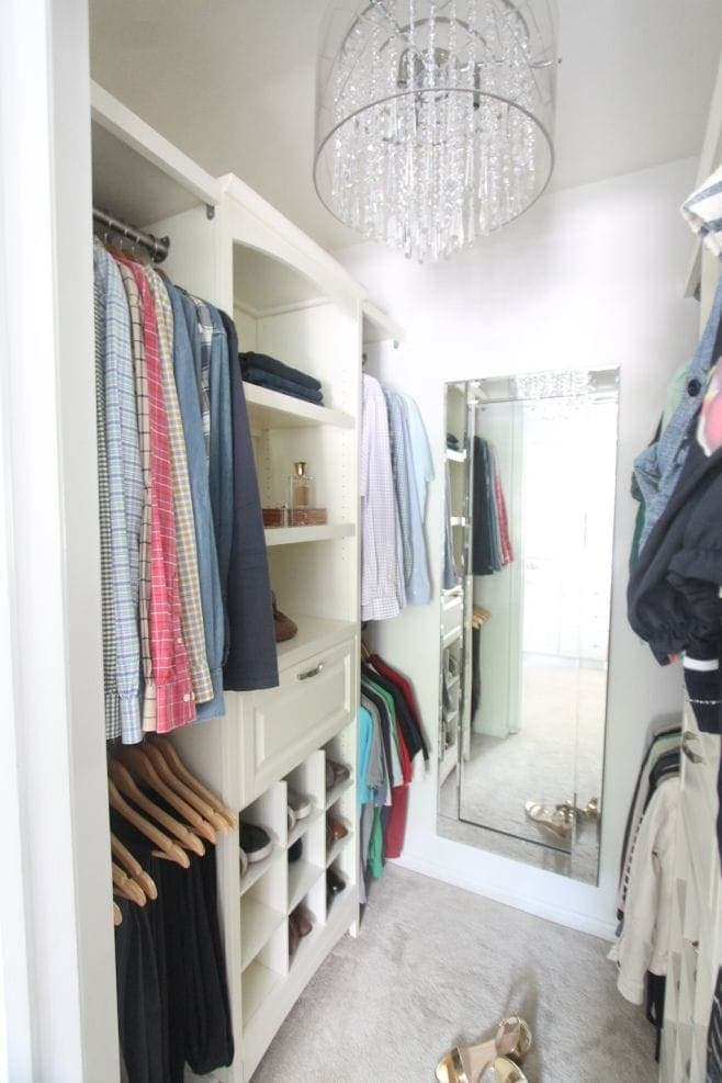 A well organized small walk in closet with a chandelier