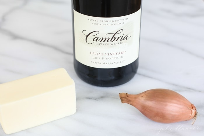 bottle of red wine, stick of butter, shallot on marble countertop