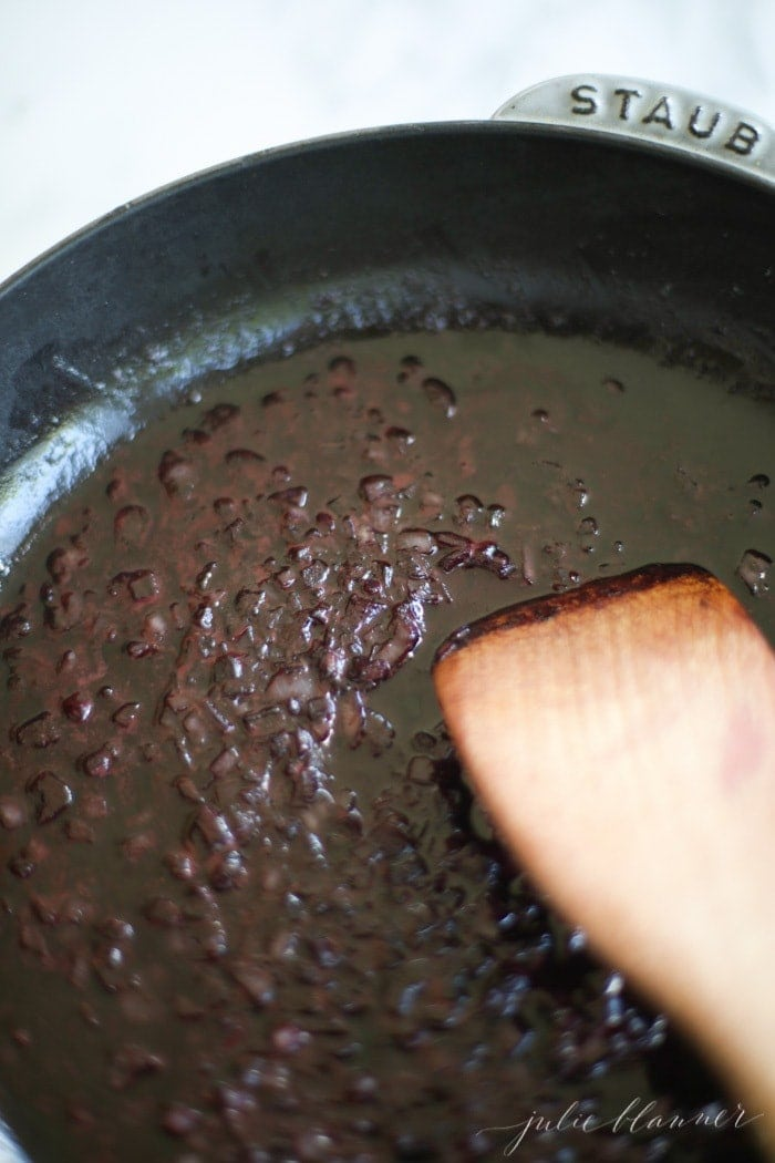 red wine sauce cooking in skillet with wooden spoon