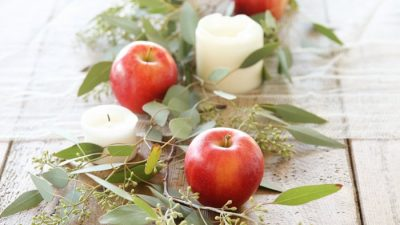 centerpiece on wood table with candles apples and eucalyptus