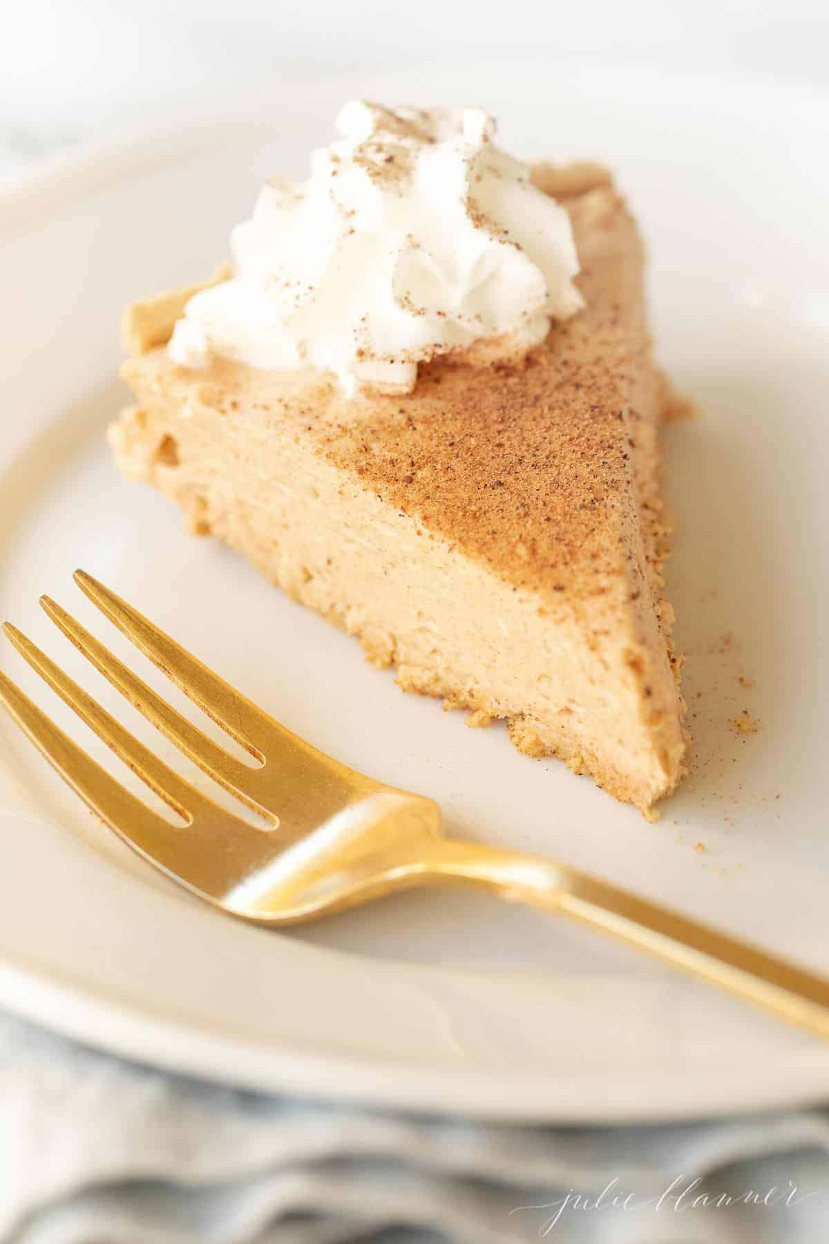White plate with a slice of no bake pumpkin cheesecake, gold fork to the side.