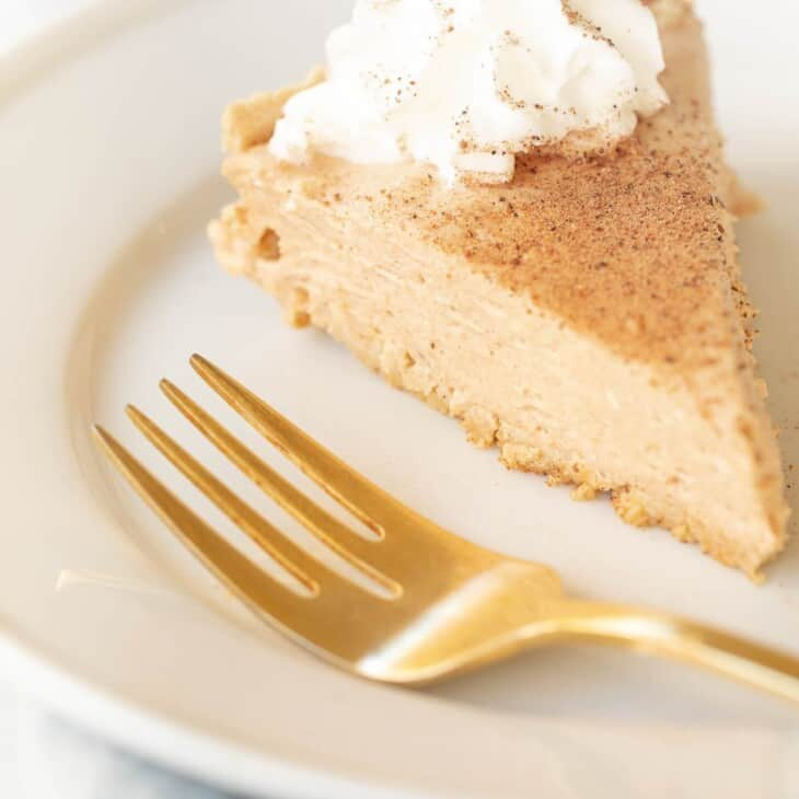 Pumpkin cheesecake topped with whipped cream on a white plate with a gold fork to the side.