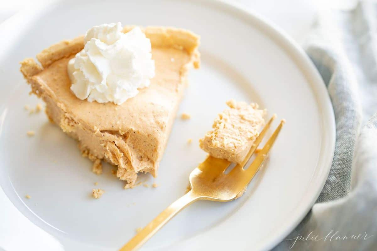 white plate with a slice of pumpkin cheesecake, gold fork has a chunk of cheesecake on it.