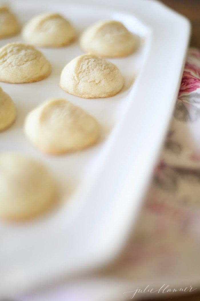 A white platter full of round browned butter sugar cookies.