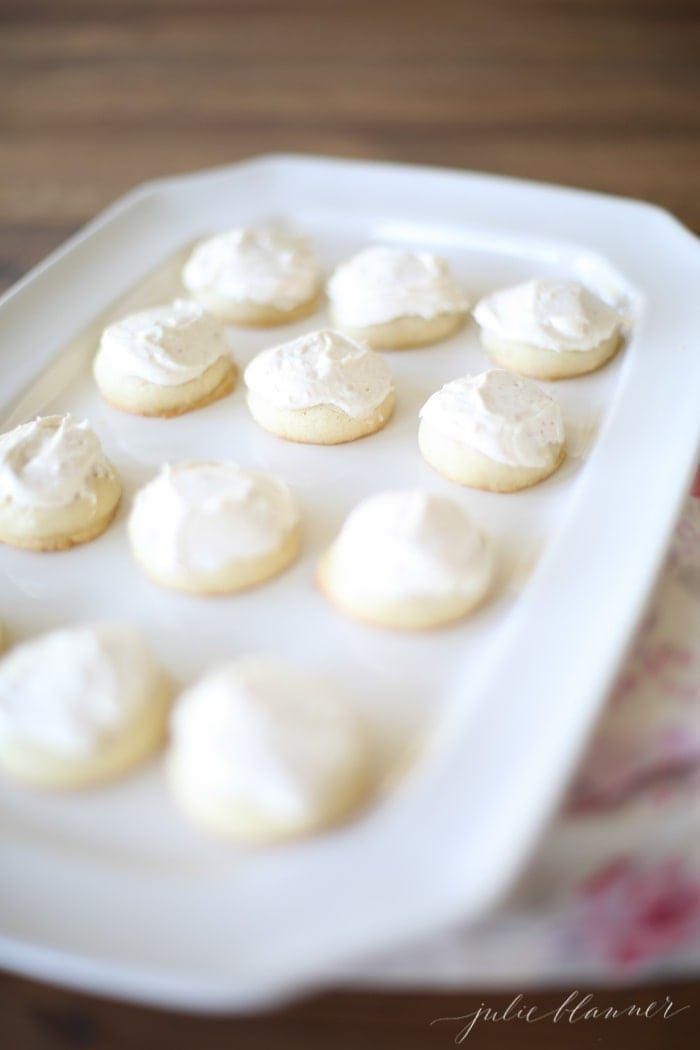 A white platter full of round browned butter sugar cookies with brown butter frosting.