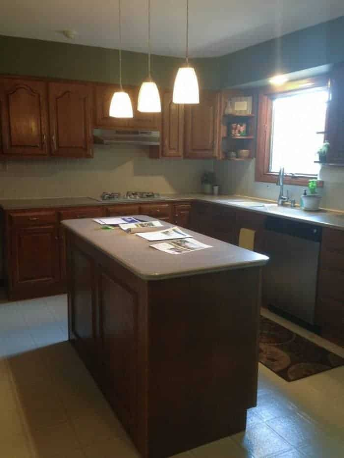 A dark and dated oak kitchen with outdated light fixtures.