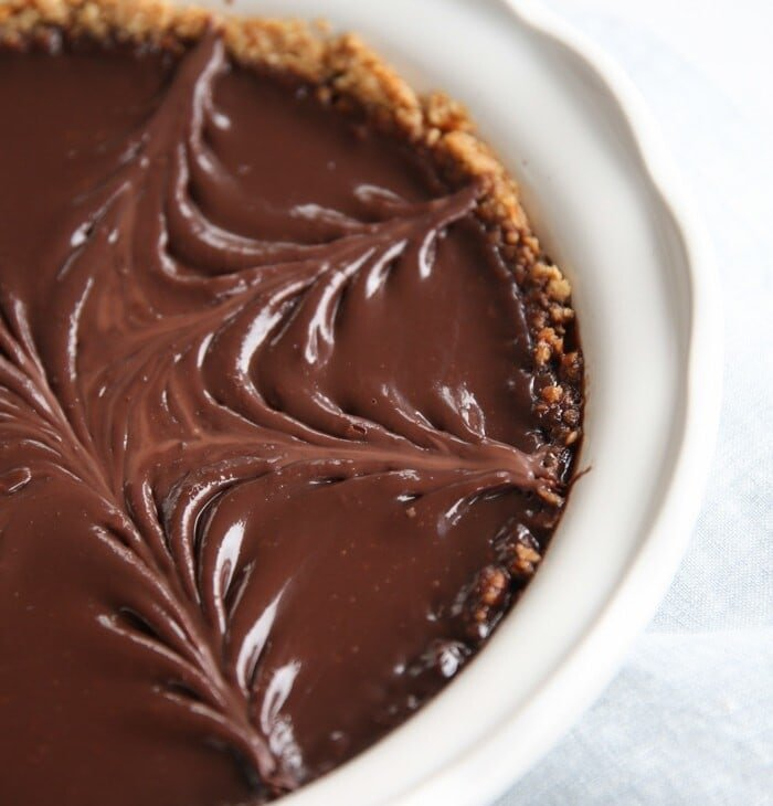 pretzel crust pie with chocolate filling in white baking dish