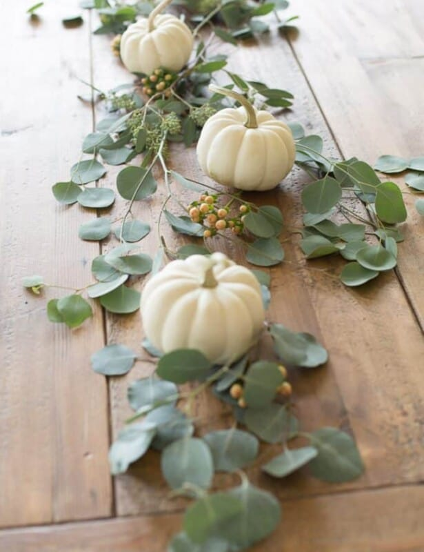 pumpkins and greenery on wood table