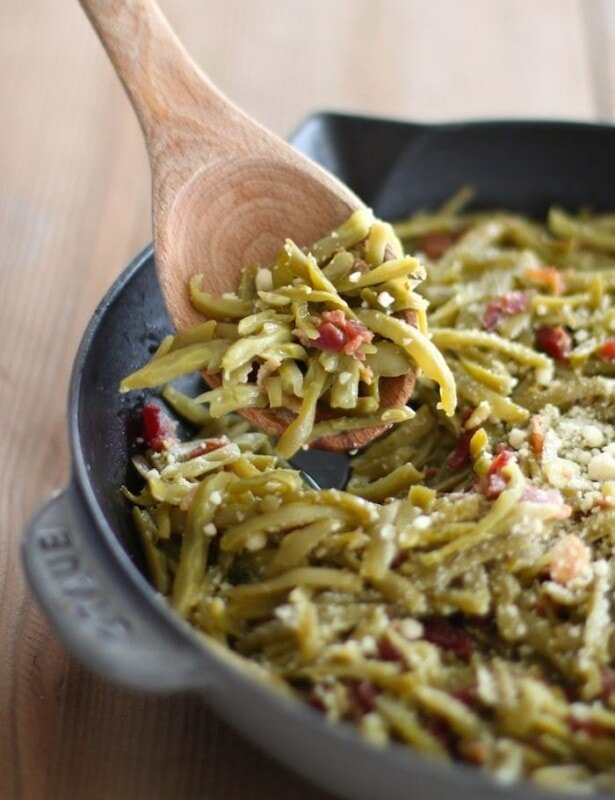 green beans with bacon in cast iron pan with wood spoon