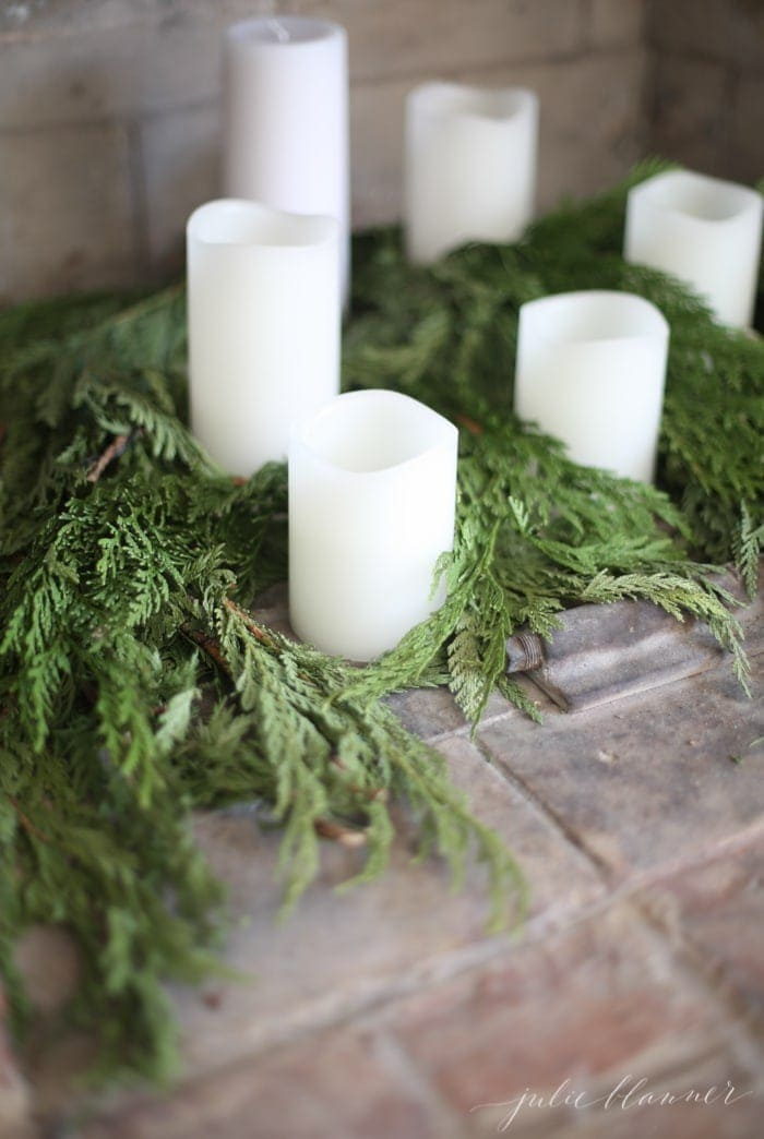 candles and greenery in fireplace
