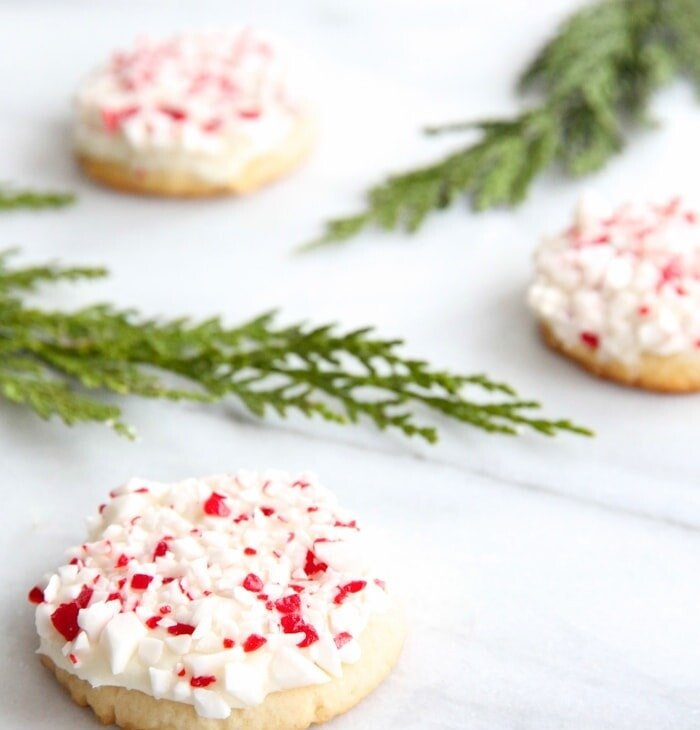 frosted peppermint cookies on marble countertop with holly leaves
